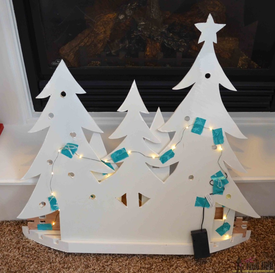Tape lights to the back. DIY Pottery Barn Kid's inspired Christmas village silhouette.