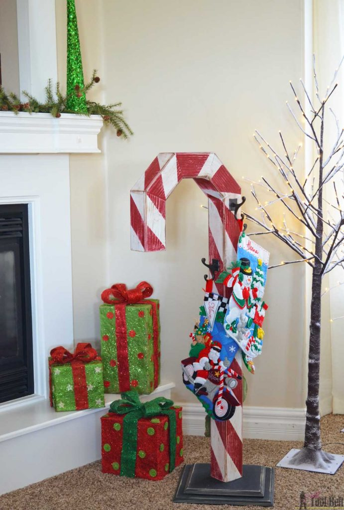 This is a perfect way to hang my Christmas stockings without a mantel! Free plans to build a DIY holiday Candy Cane stocking holder from a simple wood 4x4 post.