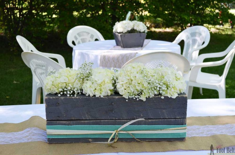 Gray planter box centerpiece with hydrangeas and baby's breath. Rustic DIY wedding decor.