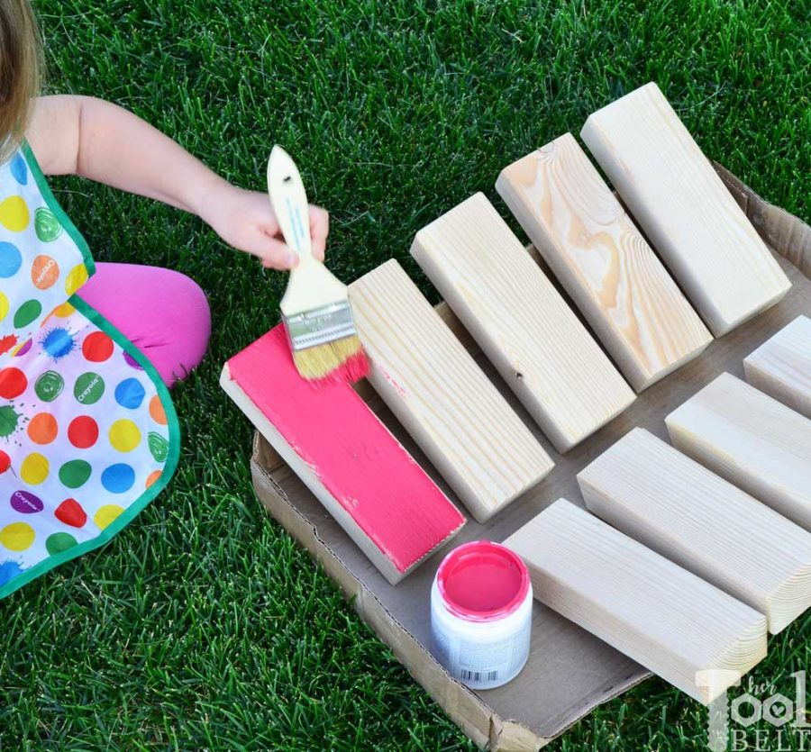 Painting the blocks colors. Make your own Giant Block Tower Builders yard game with a carrying crate that doubles as a playing stand. Add colored dice for a fun roll 'n go option to mix things up.